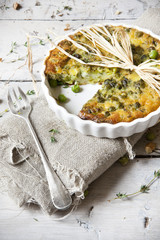 vegetables quiche with peas on baking dish with fork