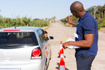 Fototapete - african instructor teaching learner driver to park a car
