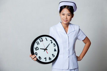 Young Asian nurse with clock