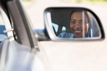 Fototapete - young african female driver looking at side mirror