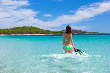 Young woman running into tropical blue sea with snorkeling gear