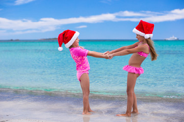 Little cute girls in Santa hats having fun on exotic beach