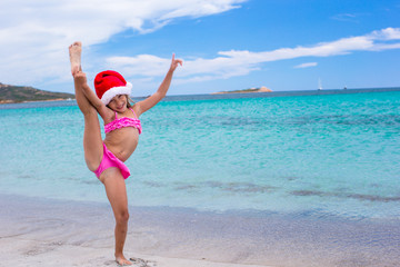 Smiling little girl making stretching exercise in Santa Hat on