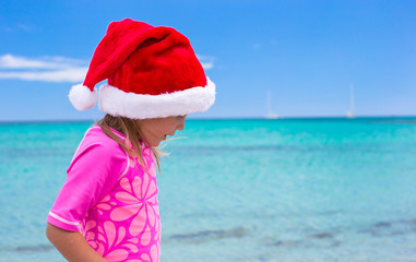 Little adorable girl wearing Santa hat at tropical beach