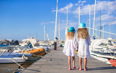 Adorable little girls walking in a port on summer day