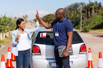 Fototapete - african girl and driving instructor doing high five