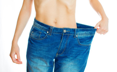 Weight loss concept. Woman wearing old jeans. Isolated on white.