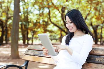 公園のベンチでタブレットPCを使う女性