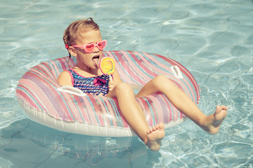 little girl with lollipop lying on the  inflatable rubber circle