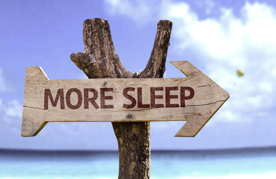 More Sleep wooden sign with a beach on background