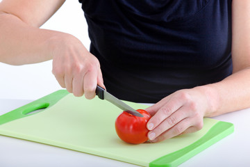 Woman with knife cut the tomato