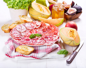 plate of various ham and salami with fresh fruits