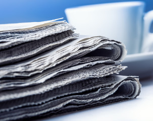 Several pieces of newspaper on a table with a cup of coffee.