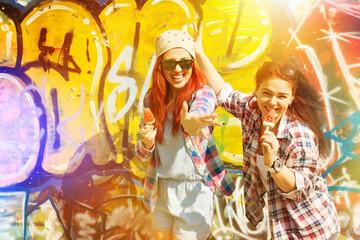 Two happy teenage girls eating ice cream by graffiti wall