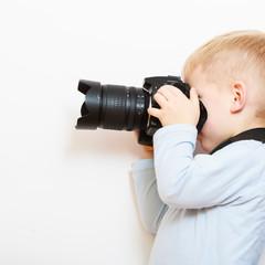 Boy child playing with camera taking photo.