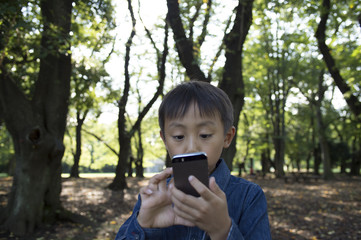 Boy that use the smartphone in the forest