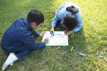 Boy and girl to be painting on the lawn