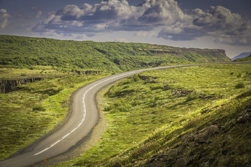 Curved shape asphalt road in high mountains of Iceland