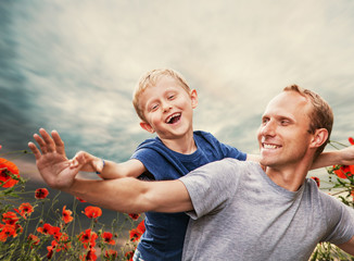 Happy smiling son with father among the poppies flowers