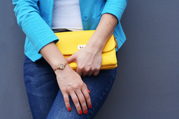 Wall Mural - The fashionable young woman  holding yellow clutch