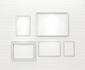 composition of white blank picture frames on white brick wall
