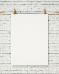 blank white hanging poster with clothespin on brick wall