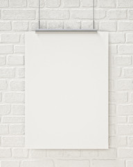 blank poster hanging on the white brick wall