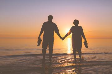 Happy senior couple silhouettes on the beach