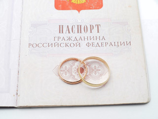 wedding rings and a Russian passport on white background