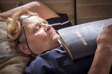 Adult woman fell asleep with a bible in her hands