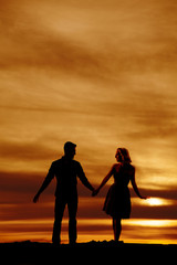 silhouette couple hold hands look at each other