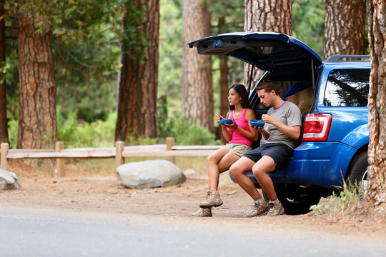 Couple on car road trip travel in eating in forest