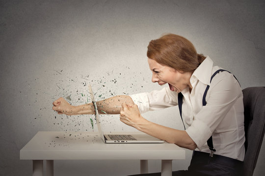Angry woman breaking computer screaming