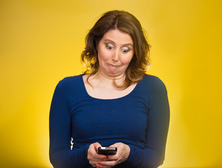 Surprised woman looking at phone seeing bad news