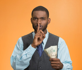 Corrupt businessman holding dollar bills showing shhh sign