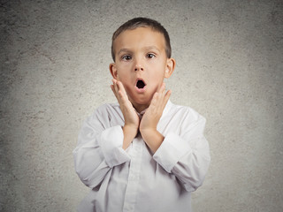 Surprised child boy with stunned face expression grey background