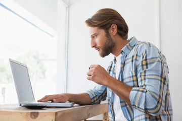 Casual man using laptop drinking espresso
