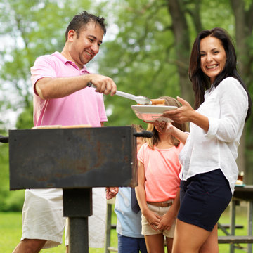 dad dishing out cooked food at family cookout