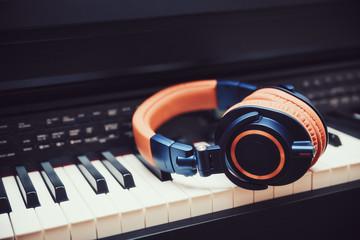 Blue-orange headphones on a digital piano keyboard
