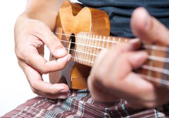Hand playing ukulele, small string instrument
