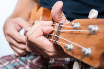 Hand playing ukulele, small string instrument