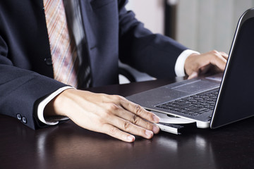 Business man holding Disk insert to laptop