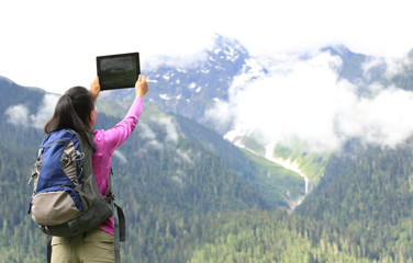 young woman tourist taking photo with digital tabelt in tibet