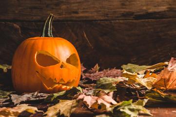 Frightening Halloween pumpkin on leaves