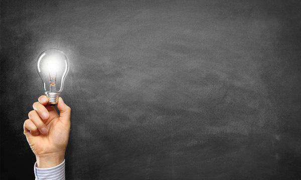 Hand holding Light Bulb / Blackboard