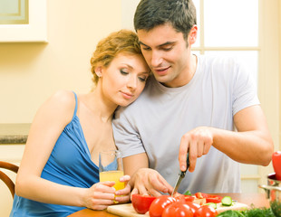 Cheerful young cooking couple at home