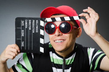 Man with baseball cap and movie board
