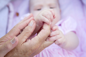 Grandmother hands holding baby hands