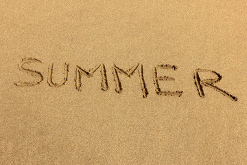 Summer - word handwritten on sand