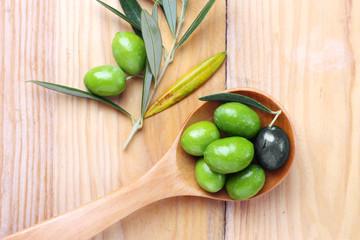 Fototapete - Olive verdi e una nera in un cucchiaio di legno